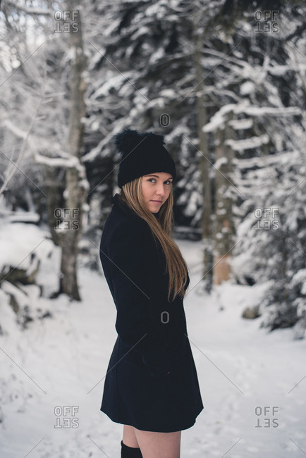 Young attractive woman in funny hat and black coat posing on forest way and looking at camera