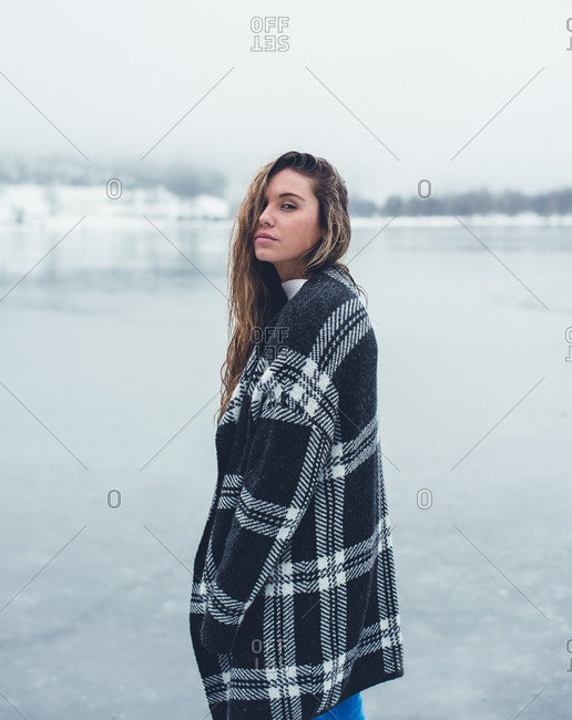 Beautiful woman with curly hair in plaid coat posing on lake and looking at camera