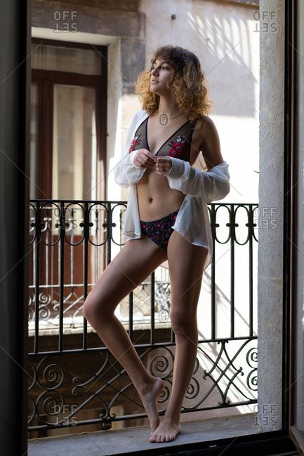 Slim girl in stylish underwear on balcony