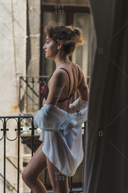 Side view of alluring girl in lace underwear and white shirt standing alone on balcony looking away in dream