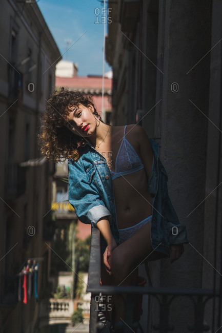 Charming girl in underwear and boots with jacket standing on balcony and smiling at camera in sunlight