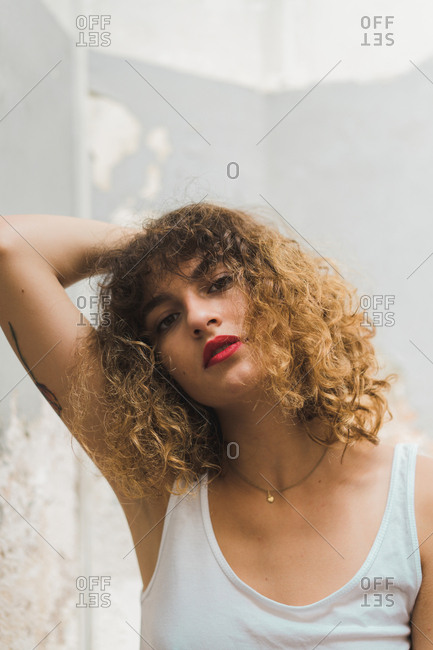 Close-up of young emotionless woman with red lipstick and voluminous curls looking at camera