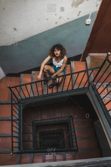 From above shot of curly woman in shorts sitting on shabby steps in hall looking up