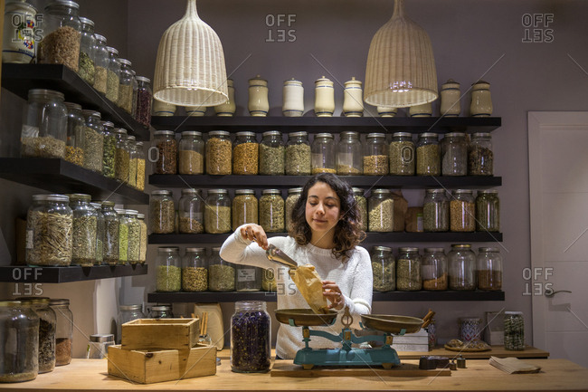 Woman putting spices to bag