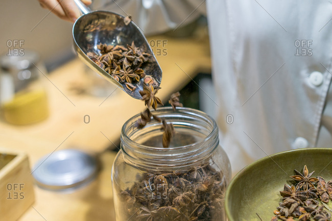 Unrecognizable seller putting anise stars to glass jar in spice shop.