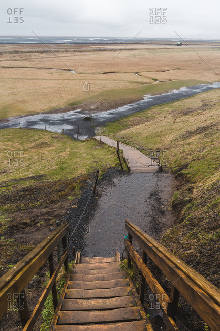 Steps of lumber stairway going down through amazing Icelandic countryside on dull day
