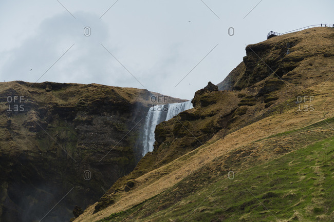 Side view of tourists walking up and down stairway in wonderful Icelandic countryside