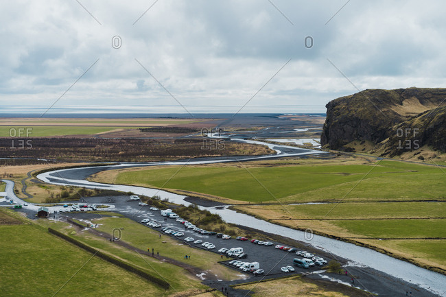 Beautiful view of fields and parking lot located near narrow river in majestic Icelandic countryside