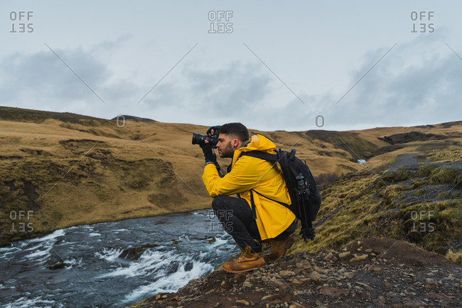 Side view of young photographer using camera to make photos of magnificent Icelandic countryside while sitting near creek