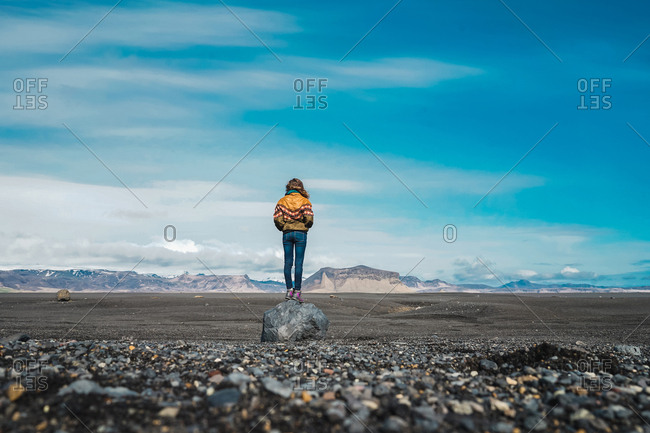 back view of young woman standing in amazing countryside and enjoying view while traveling through Iceland