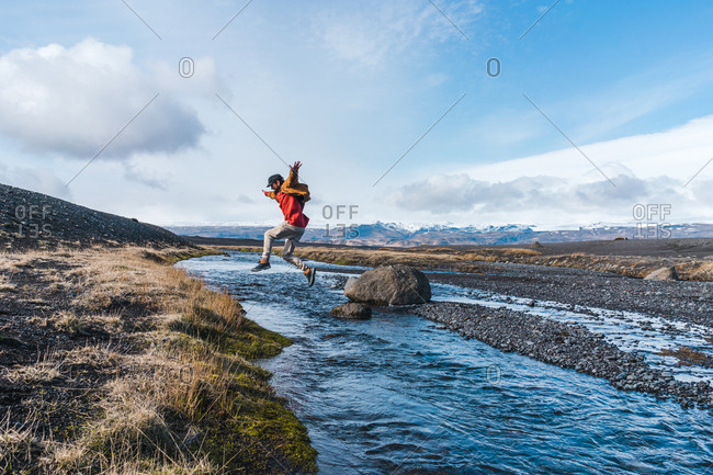 Side view of young man in casual outfit jumping over creek while traveling through wonderful Icelandic countryside