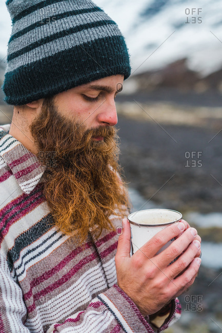 Attractive bearded man holding mug with hot drink and looking away while leaning on metal fence not far from small cottage in Icelandic countryside