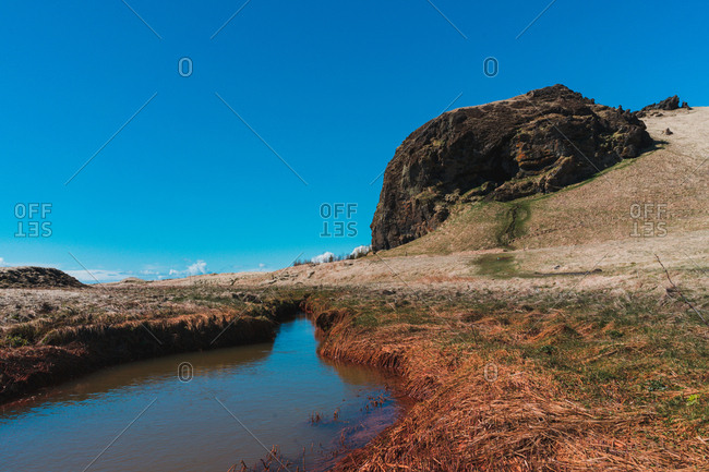 Beautiful landscape of low tide on coast with reflecting blue sky on mountains background in Iceland