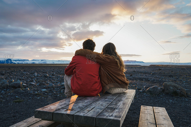 Back view of lovers sitting on wood table embracing and looking on beautiful sunset in Icelandic valley