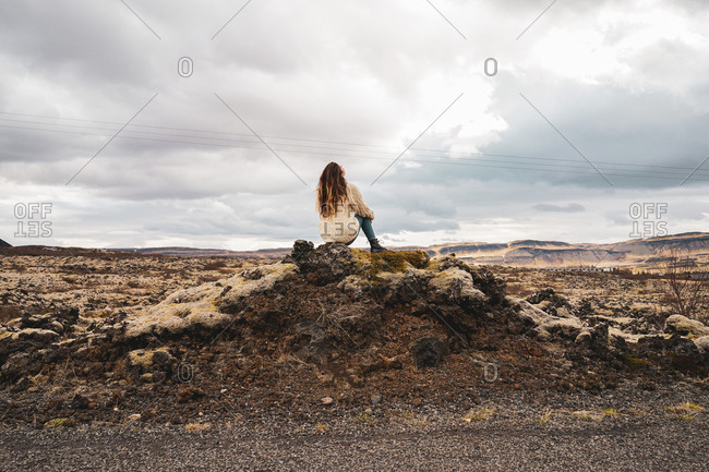 Woman sitting on picturesque stony background