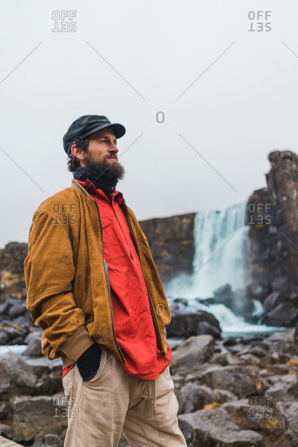 Handsome bearded man looking away while standing on background of beautiful waterfall during trip through Iceland.