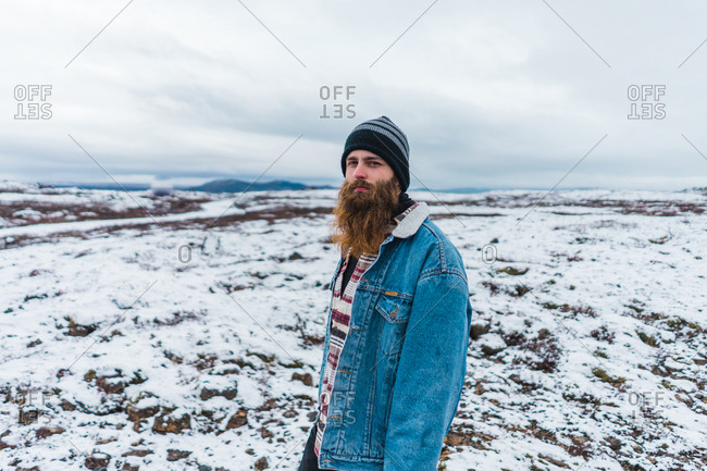Side view of bearded man in warm clothes looking up while standing on field covered with snow during trip through Iceland.