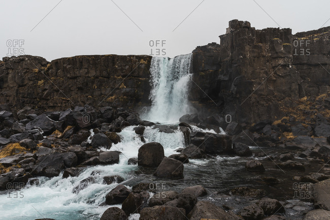 Picturesque view of water falling from rocky cliff in Iceland.