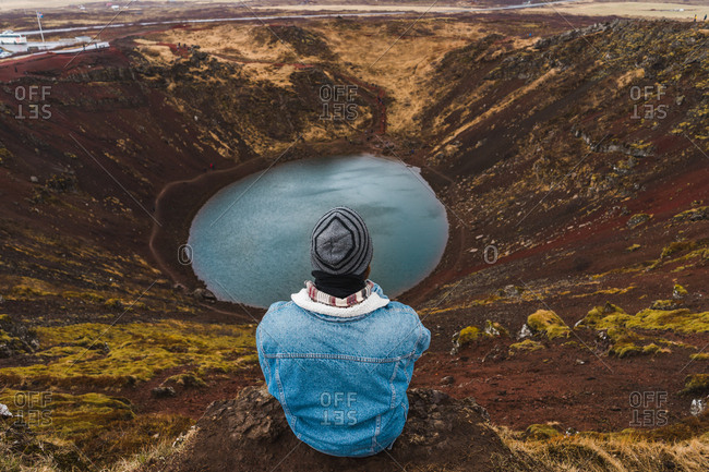Back view of faceless man in warm clothes sitting on rim of open pit and looking at small lake while traveling through Iceland.