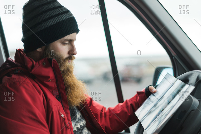 Crop side view of bearded male in red jacket driving car and looking at road map in Iceland