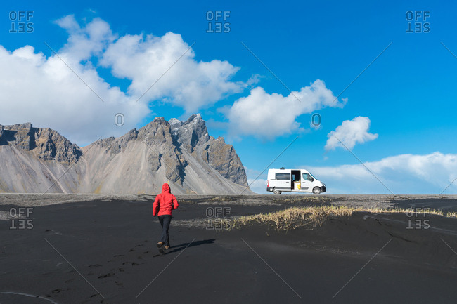 Back view of person in red jacket running to car on black sand beach with mountains in Iceland