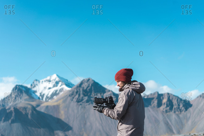 Side view of  bearded male in hat holding camera with professional lens and looking away in Iceland
