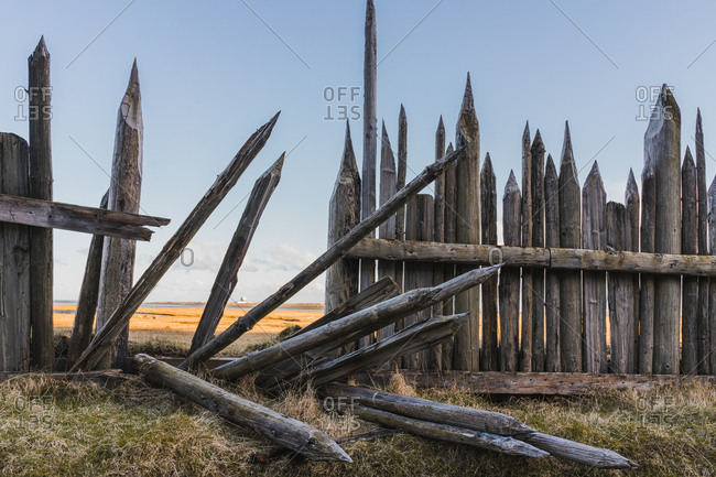 Old wooden fence with sharp tops on bluff overlooking expansive valley in Iceland