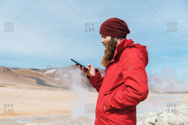 Side view of bearded male in warm bright clothes using mobile phone standing in front of steaming hot spring in Namaskardh in Iceland