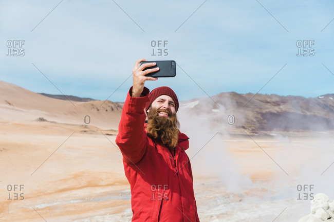Man standing with smartphone at geyser