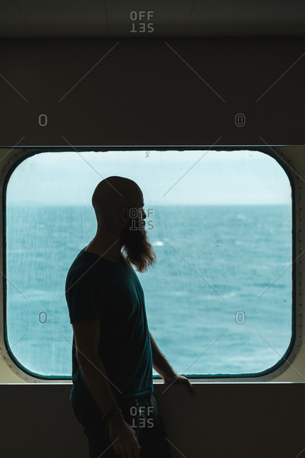 Side view of bearded man standing at ship window and looking away at the ocean.