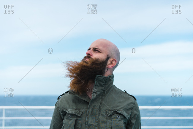 Thoughtful bearded man standing on ship deck and looking away at the ocean.