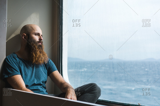 Thoughtful adult bearded man sitting at the window and looking away.