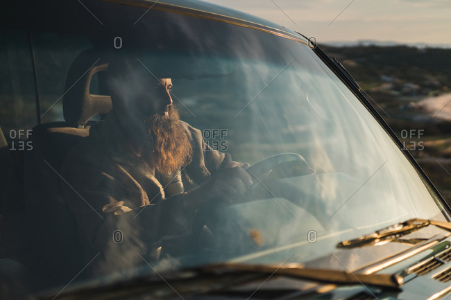 Side view of hairless bearded man driving a car on coast at the ocean in sunset lights.