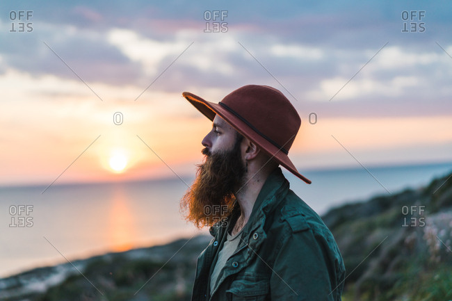 Side view of thoughtful bearded man in hat standing on seashore on background of the sunset.