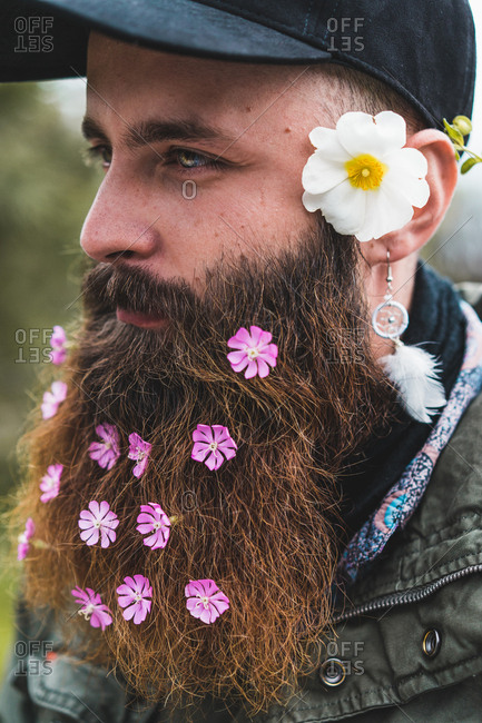 Cheerful adult man with soft flowers in beard taking selfie with smartphone in nature.