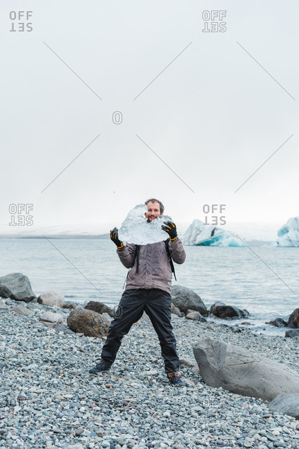 Man standing by water holding ice piece above head