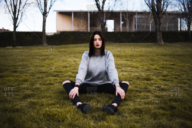 Serious brunette in casual outfit and with dark makeup sitting on green grass looking at camera.