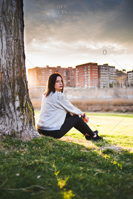 Side view of casual brunette sitting under tree on lawn against city in sunset and gloomy sky.