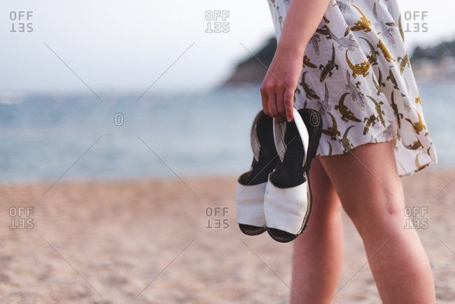 Side view of crop woman carrying sandals while walking on sandy beach at the ocean