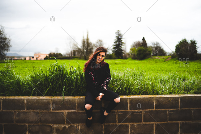 Side view of pretty woman in black sitting on brick wall with lush green grass and gloomy sky on background.