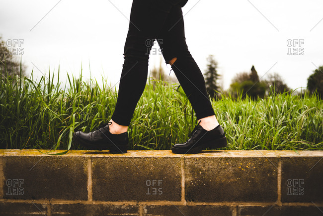 Crop side view of woman in black jeans and shoes walking on brick wall with green grass on background.