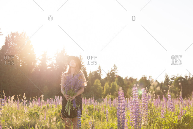 Anonymous woman in hat and dress standing with bunch of flowers in blooming field in bright back lit