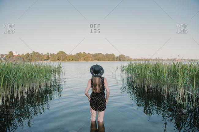 Stylish woman in bright sunshine on shore