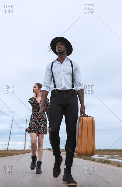 Multiethnic couple with suitcase walking on asphalt road in the field.