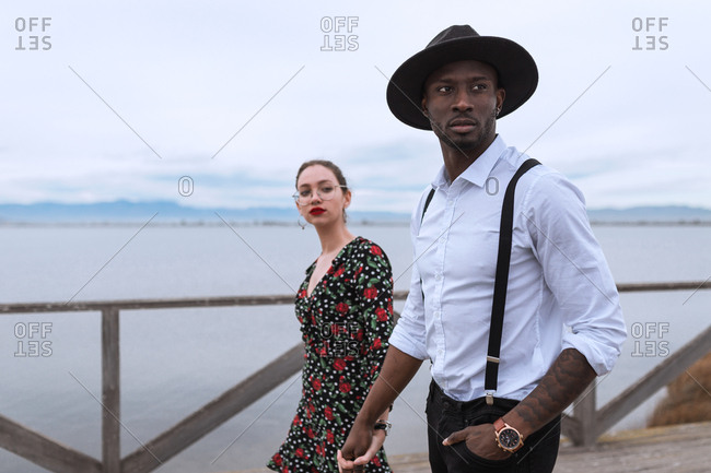 Side view of multiracial couple leaning on handrail and looking away in nature.