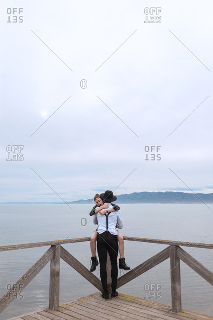 Side view of multiethnic couple embracing at handrail at the lake.