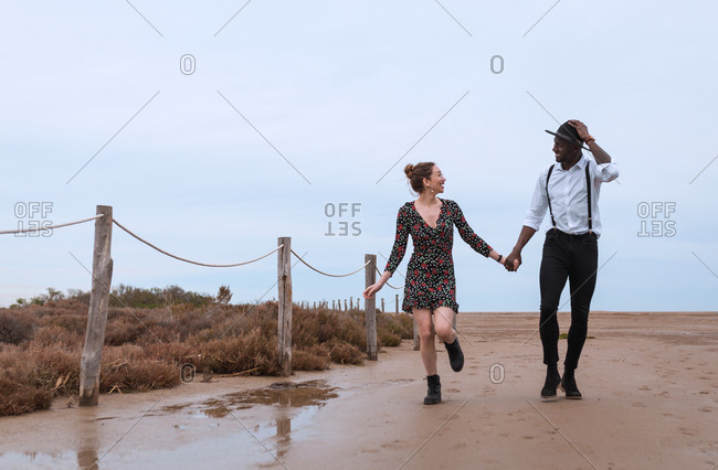 Side view of multiracial couple standing and bonding at fence in nature.