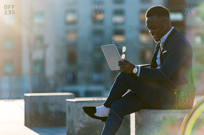 Ethnic businessman sitting with laptop on street