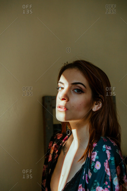 Attractive young woman with sun flare on face looking at camera at home.