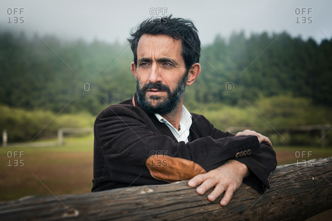 Thoughtful bearded mature man in jacket leaning on wood fence looking away against misty rural woods